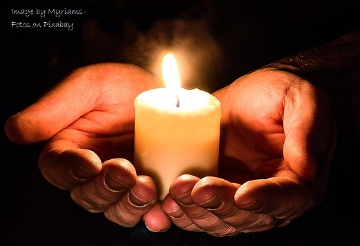 image of hands holding a lit candle in the dark