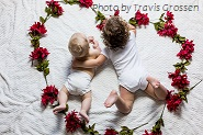 image of babies laying on blanket surrounded by flowers laid out in a heart shape